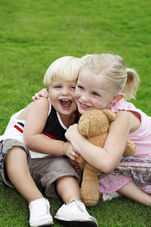 toy bear: Girl hugging little boy and toy bear Stock Photo