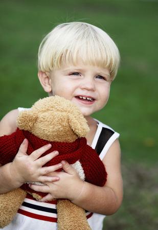 Little boy hugging a toy bear photo