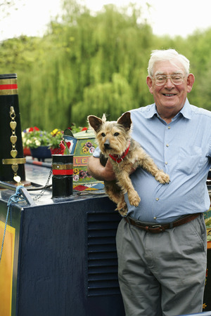 Senior man posing with his dog on the houseboat photo