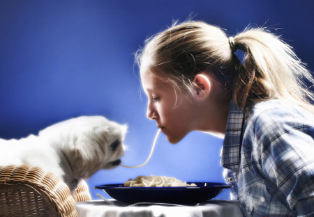 Girl sharing spaghetti with her dog photo