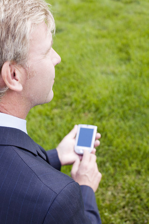 handheld device: Businessman holding a handheld device Stock Photo