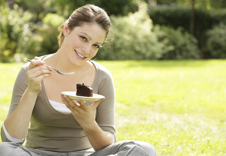 indulging: Young woman indulging in a piece of chocolate cake Stock Photo