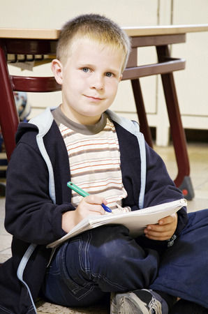 Boy looking at the camera while holding a pen and a book photo