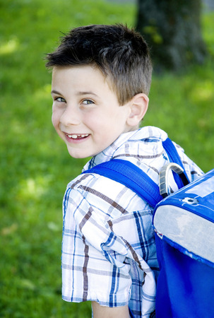 Boy carrying school bag on his back photo