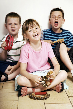 Children singing while playing musical instrument photo