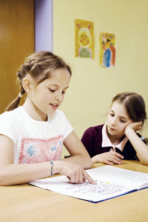revision book: Girl watching her friend reading book Stock Photo
