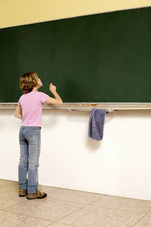 Girl standing in front of blackboard holding a chalk photo