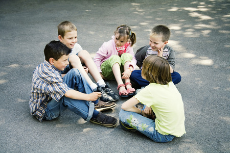 recess: Children sitting in a circle playing Stock Photo