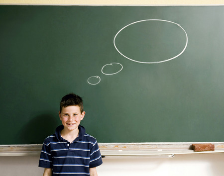 Boy standing in front of a blackboard with thought bubble photo
