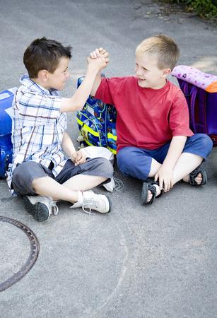 h�ndchen halten: Jungen H�ndchen haltend beim Sitzen zusammen Lizenzfreie Bilder