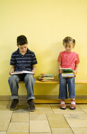 revising: Boy and girl sitting on the bench with books on the lap