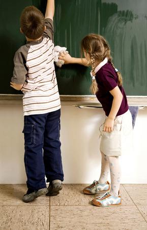 Boy and girl washing the blackboard Stock Photo