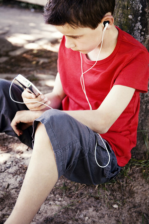 portable mp3 player: Boy listening to music on a portable MP3 player