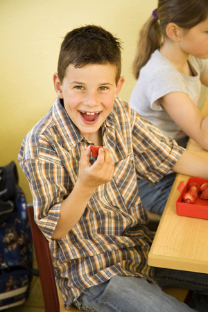 Boy smiling at the camera while holding a strawberry photo