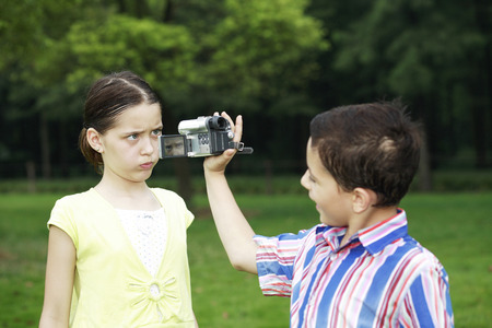 Boy recording images of girl making a face Stock Photo