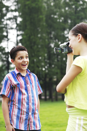 Girl recording images of boy making a face photo