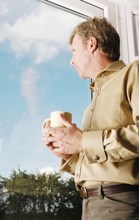 Businessman holding a cup of drink while looking out of the window photo