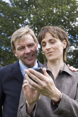 handheld device: Businessman and woman looking at handheld device
