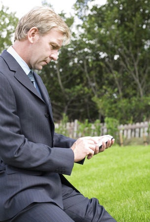 handheld device: Businessman using a handheld device Stock Photo