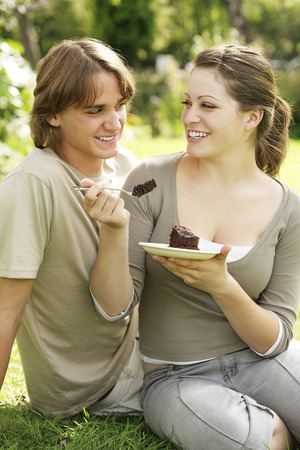 indulging: Couple indulging in a piece of chocolate cake