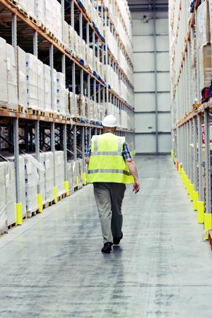 Man walking past warehouse goods photo