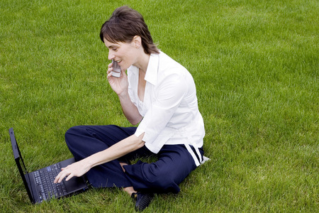 Woman talking on the mobile phone while using laptop in the park photo