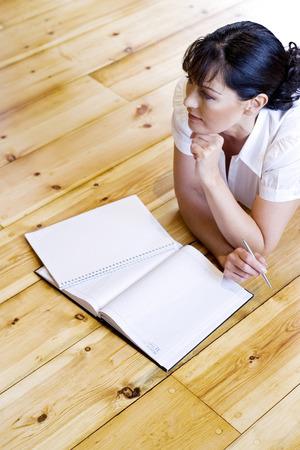 lying forward: Woman lying forward on the floor thinking