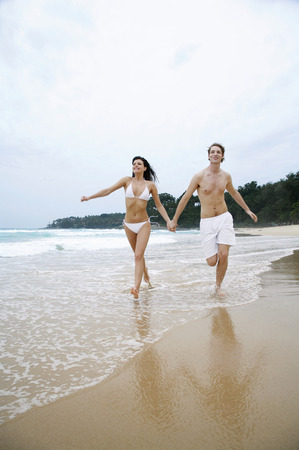 Couple holding hands while running on the beach photo