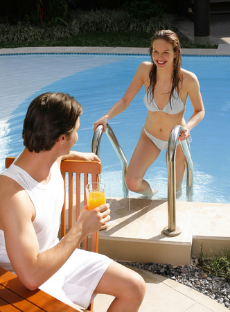 Man enjoying drink by the pool side with his girlfriend climbing out from the pool photo