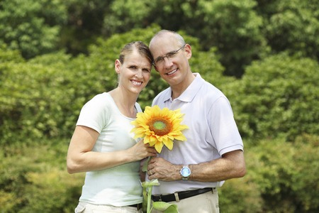 Husband and wife holding a sunflower photo