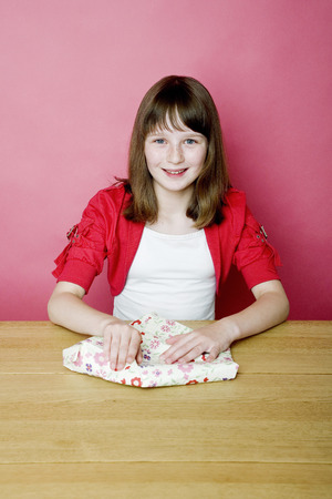 unwrapping: Girl unwrapping present Stock Photo