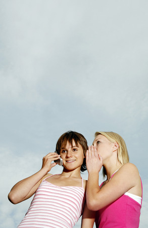 Woman whispering to her friend who is talking on the mobile phone photo