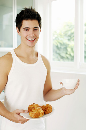 Man holding a plate of croissants and a cup of coffee photo