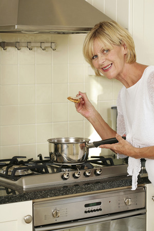 Senior woman cooking in the kitchen photo