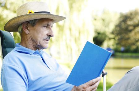 Senior man sitting on a chair reading book photo