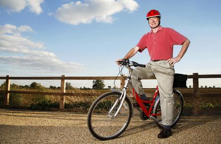 safety helmet: Senior hombre con casco de seguridad sentado en una bicicleta Foto de archivo