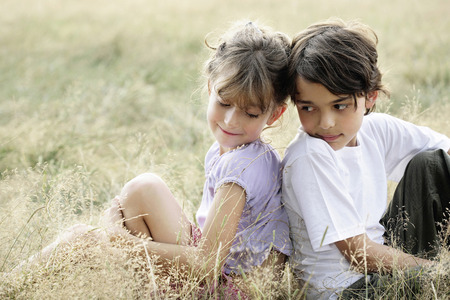Children sitting back-to-back each other