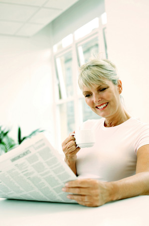Woman holding a cup while reading newspaper photo