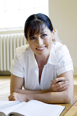 lying forward: Woman lying forward on the floor smiling at the camera