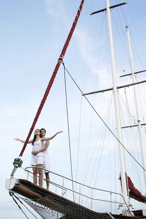 Couple standing on the edge of yacht photo