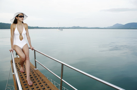 Woman with hat and sunglasses sailing on yacht photo