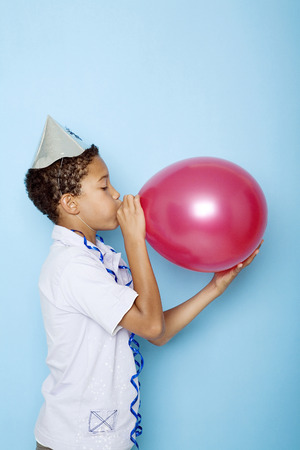 Boy blowing up a balloon Stock Photo