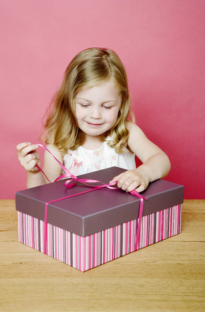 unwrapping: Girl unwrapping her present