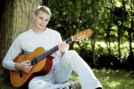 Teenage boy playing with a guitar photo