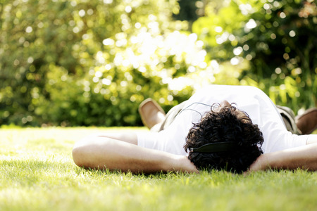Man lying on the grass listening to music on the headphones photo