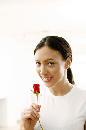 Woman smiling while holding a red rose photo