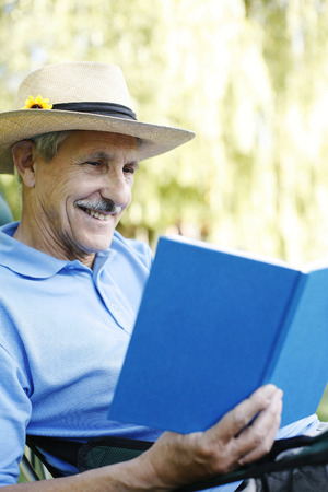 Senior man with hat reading book photo