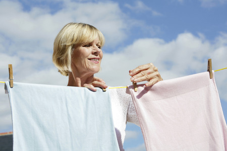 hanging clothes: Senior woman hanging clothes on the clothesline
