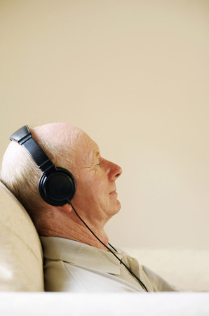 Senior man closing his eyes while listening to music on the headphones photo