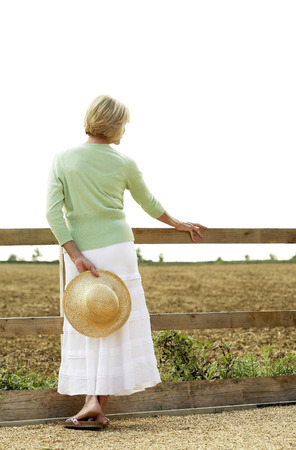 Senior woman holding a hat on her back photo